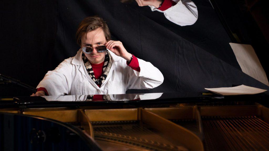 Zacharias mit Kittel, Sonnenbrille und Klaviatur-Schal am Flügel.